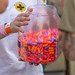 Woman from the first aid team offers colorful ear plugs from a big plastic jar to the visitors of Tomorrowland