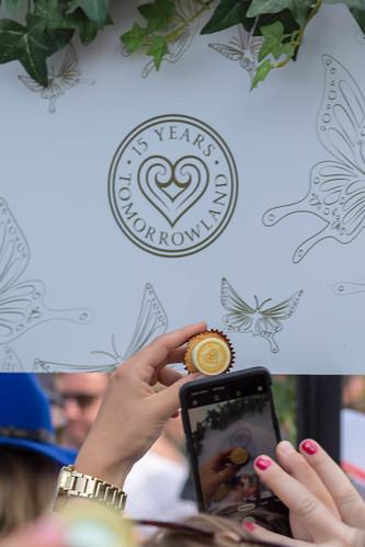 """Frau macht Foto von Cupcake zum 15-jährigen Jubliäum vor Schild """"15 years Tomorrowland"""""""