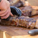 Nahaufnahme von Mann der ein großes Stück OFYR-Grillfleisch in Stücke schneidet auf Holztisch