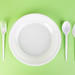 Plastic dishes on green background