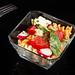 Tomato Radishes Rukola and Cheese salad above black background