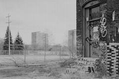 proximity. (jonathancastellino) Tags: detroit michigan abandoned derelict decay landscape leica film expired analog analogue ilford xp2 fence poll door graffiti