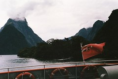 Milford Sound (Chloué) Tags: analogphotography analog filmphotography filmisnotdead 135 35mm argentique kodak olympusom1 olympus newzealand milfordsound southisland southland moutains southernalps fiord nature outdoor boat flag aotearoa