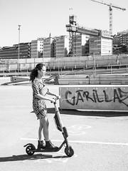 Scooter (Dare to share) Tags: stockholm stockholmcounty sweden scooter electricvehicle transportation city urban girl woman architecture gondolen europe jonasthoren street bw blackandwhite
