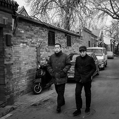 Bro (Go-tea 郭天) Tags: pékin républiquepopulairedechine beijing hutong old ancient narrow alley traditional tradition history historical historic building construction pavement bricks cold winter sun sunny shadow friend 2 together men walk walking portrait cap cars street urban city outside outdoor people candid bw bnw black white blackwhite blackandwhite monochrome naturallight natural light asia asian china chinese canon eos 100d 24mm prime