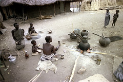 79-383 (ndpa / s. lundeen, archivist) Tags: nick dewolf color photograph photographbynickdewolf 1976 1970s film 35mm 79 reel79 africa northernafrica northeastafrica african ethiopia ethiopian southernethiopia riverlife village people localpeople villagelife utensils bowl bowls cooking openfire fire flames firepit woman mother nursing child baby infant children kids eat eating youngwoman necklaces beads pail bucket women localwoman localwomen barefoot barefeet building house home thatchroof thatchedroof tribe southerntribe