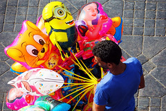 Like his own, personal, harem - Main Square of the Medina, Marrakesh, Morocco (TravelsWithDan) Tags: man balloons fromabove colors balloonsalesman mainsquare medina marrakesh morocco city urban africa canong3x candid