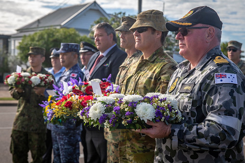 Members participating nations from exercise TS 19 hold wreaths during a memorial ceremony