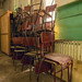 A stack of classroom chairs at an abandonded school