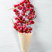 Waffle cone filled with red currant berries on white wooden background