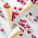 Top view of waffle cone with frozen raspberry berries on white wooden background