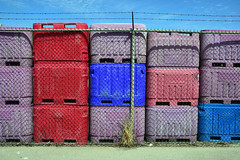 Waiting (James_D_Images) Tags: storage bins fisheries chainlinkfence barbedwire fence plastic stacked red blue purple asphalt bluesky clouds steveston britishcolumbia abstract pattern lines