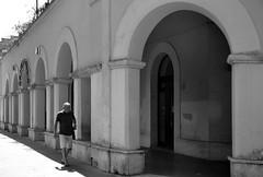 Linee di fuga (Colombaie) Tags: roma lido ostia mare estate 2019 architettura novecento gente persone street barocchettoromano ritratto uomo maschio camminare unaware bn bw passante portici arco arcate piazzale vecchia stazione