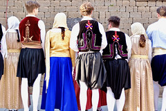 Assortment (fillzees) Tags: candid street costume girl guy woman dancer traditional greek back wall colorful folk dress scarf vest stone hosiery design headgear