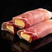 Rolled Pork Ham with yellow Cheddar cheese above black background