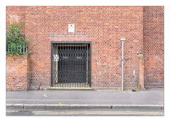 The Built Environment, East London, England. (Joseph O'Malley64) Tags: thebuiltenvironment newtopography newtopographics manmadeenvironment manmadestructure building structure artdeco artdecobuilding eastlondon eastend london england uk britain british greatbritain wall walls brickwork bricksmortar cement pointing redbricks concertinagate doorway doubledoors woodenpanelleddoors entrance exit signs signage step healthsafetysigns signpost noloadingatanytime cctvwarningsign securityfence spikedfencing securityspikes ivy shrub weeds tarmac granitekerbing draincover doubleyellowlines noparkingatanytime parkingrestrictions plasticbag litter architecture urbanarchitecture architecturalfeatures architecturalphotography documentaryphotography britishdocumentaryphotography fujix fujix100t accuracyprecision
