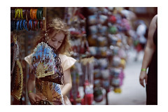 Mom, can I have one? Dreams of a princess. (Gudzwi) Tags: sommerimpression summerimpression licht leuchten leuchtendeaugen wünsche träume souvenir toskana siena allessoschönbunthier bokeh closeup nahaufnahme unschärfe bunt sonne flirrend verkaufsstand geschäft souvenirladen mutterundtochter mädchen porträt street strasenfotografie leute menschen spitze shop lace fächer fan light shine brighteyes wishes dreams tuscany everythingssocolorfulhere close fuzziness colorful sun shimmering stall business motheranddaughter girl portrait streetphotography people