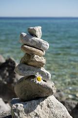 Stones (DJ Wolfman) Tags: stones stackedstones water blue green sunlight mackinacisland summer summerinmichigan daytime micro43 olympus olympusomd em1markii zuiko 1240mmf28
