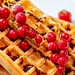 Red currant on waffles with chocolate topping close-up