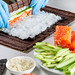 Cook preparing sushi with salmon and avocado