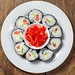 A top view of a plate of Maki rolls and pickled pink ginger