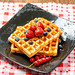 Belgian waffles with blueberries, strawberries and red currants on a black plate