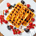 Crispy Belgian waffles with chocolate topping and ripe berries on a white plate. Top view
