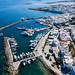 Luftbild von weißen Kalksteinhäusern am Küstenabschnitt und  Segelboote im Hafen im Mittelmeer, vor Naoussa in Griechenland