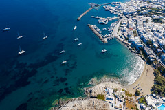 Aerial view of the village Naoussa on the Cyclades island Paros, Greece, with harbour and old Venetian castle ruin, in the bay Ormos Naousia