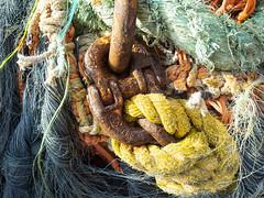 P6050145.sm (DanaStyber) Tags: commercialfishingsupplies linesandrope twisted colorful orangeandblue rustylinks wharf industrialphotography closeup