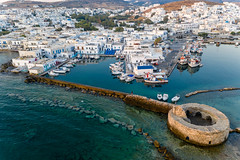 Aerial view of a harbour basin at the picturesque island town Naoussa on Paros (Greece) & ruins of an old Venetian castle in the Mediterranean Sea
