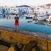 Mann steht auf einer Mauer im Mittelmeer, vor dem Hafen der griechischen Stadt Naoussa und macht Luftaufnahmen mit der Drohne DJI Mavic 2