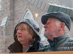 Perusing the Menu in the Rain - Dingle, Ireland (TravelsWithDan) Tags: couple candid rain outdoors city urban dingle ireland europe middleaged wet cold canong9x reading restaurant