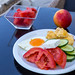 Healthy snack with fresh tomatoes, cucumber, feta cheese, scrambled eggs and watermelon
