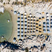 Aerial view shows the rocky beach in Kolympithres on Paros, with parasols on the white sandy beach at the green Mediterranean Sea