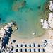 Luftaufnahme zeigt eine Frau die alleine im grünen Wasser des Mittelmeers schwimmt, in der Bucht am Strand Kolimbithres der griechischen Insel Paros