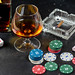A glass of cognac with poker cards, money and chips