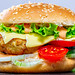 Fast food. A big burger with cutlet, cheese and vegetables