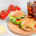 A glass of Cola with ice and fresh burgers on a round kitchen Board