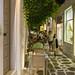 Touristen in typischer, Gasse mit Tischen in der Küstenstadt Naoussa auf Paros