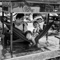 Pride and happiness (John Riper) Tags: johnriper street photography straatfotografie square vierkant bw black white zwartwit mono monochrome candid john riper xt3 fujifilm siem reap cambodia fun cambodian kids father joy proud smile hammock stand