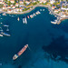 Aerial photo of the shore of Greek island Spetses in summer & boats and cargo ship in the harbour in the blue Aegean Sea