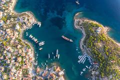Luftbild der mediterranen Insel Spetses, Griechenland, mit Küstenweg und Ankerplatz im Argolischen Golf und der Kirche Agios Nikolaos