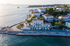Aerial view of a coastal path & Church at Agios Mamas Beach, next to aristocratic villas on the Mediterranean island Spetses
