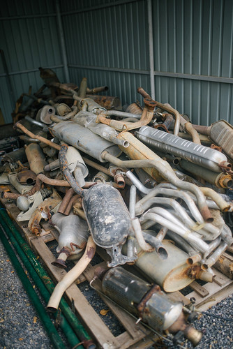 A bunch of old and rusty exhaust pipes at a car work shop