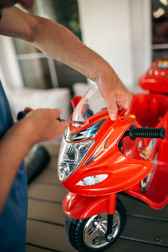 Man assembling a red motorcycle toy with a screwdriver