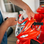 Man assembling a red motorcycle toy with a screwdriver thumbnail