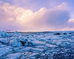 Glacier under a Pink Sky (Caleb Bertolini) Tags: iceland olympus sky blue white water bay ocean ice glacier rocks rock landscape nature natural scenery frozen golden circle cloud clouds climate change cold mountain mountains winter snow horizon black sand outside pink