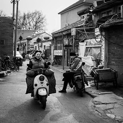 Because I'm happy... (Go-tea 郭天) Tags: pékin républiquepopulairedechine beijing hutong narrow alley old ancient construction building pavement bricks traditional tradition history historical historic sun sunny shadow winter cold woman lady motorbike motorcycle ride riding rider happy smile face portrait movement street urban city outside outdoor people candid bw bnw black white blackwhite blackandwhite monochrome naturallight natural light asia asian china chinese canon eos 100d 24mm prime