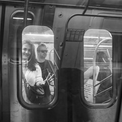 A Passing Train (John St John Photography) Tags: streetphotography candidphotography ftrain nyctransitauthority subway train passing windows youngwoman smiling commuters reflections bw blackandwhite blackwhite blackwhitephotos johnstjohnphotography